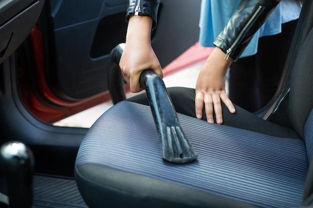 Vrouw schoonmaken, stofzuigen interieur van de auto door stofzuiger, transportconcept Premium Foto