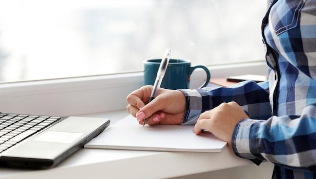 Vrouw schrijft in notitieblok Gratis Foto