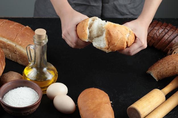 Vrouw sneed brood in tweeën op donkere tafel met eieren, meelkom en glas olie. Gratis Foto
