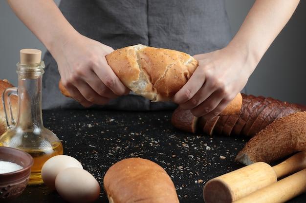 Vrouw snijden brood in tweeën op donkere tafel met eieren, meelkom en glas olie. Gratis Foto