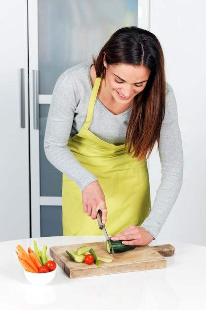 Vrouw snijden komkommer en groenten Gratis Foto