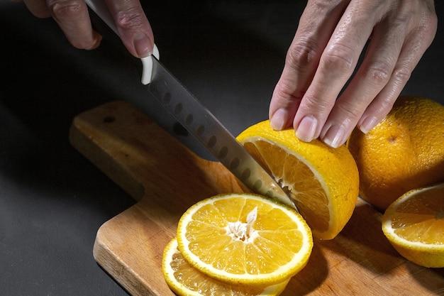 Vrouw snijden verse gezonde stukjes sinaasappel op een houten bord Premium Foto