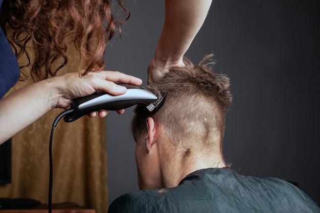 Vrouw snijdt een man met een trimmer in een kapper. stijlvol kapsel. Premium Foto