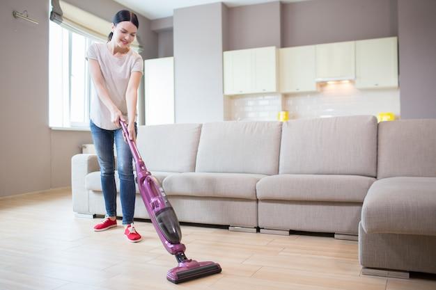Vrouw staat in een studio-appartement en het schoonmaken van de vloer. ze gebruikt daarvoor een stofzuiger. meisje kijkt naar beneden. Premium Foto