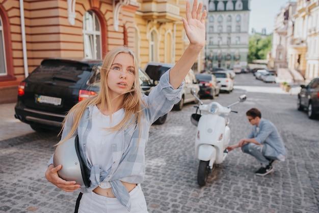 Vrouw staat op weg en zwaait met haar hand Premium Foto