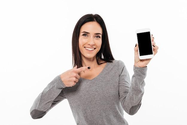 Vrouw status geïsoleerd tonend vertoning van mobiele telefoon. Gratis Foto