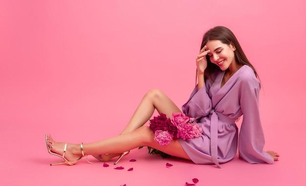 Vrouw stijl in jurk met bloemen op roze achtergrond Gratis Foto