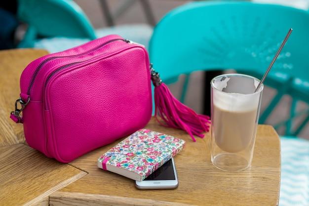 Vrouw stijlvolle accessoires op tafel in café, lente zomer modetrend Gratis Foto