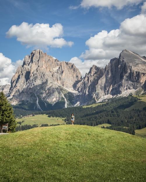 Vrouw stond op een heuvel met de plattkofel-berg als achtergrondkleur in compatsch, italië Gratis Foto
