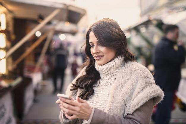Vrouw stond op straat en met behulp van slimme telefoon tor sms'en. Premium Foto