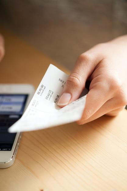 Vrouw telt geld met haar telefoon Gratis Foto