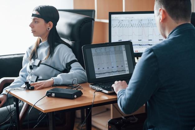 Vrouw testen op trouw. meisje passeert leugendetector in het kantoor. vragen stellen. polygraaftest Gratis Foto