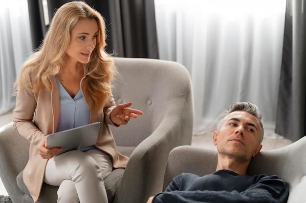 Vrouw therapeut praten met man bank opleggen Gratis Foto