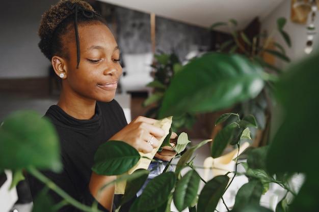 Vrouw thuis. meisje in een zwarte trui. afrikaanse vrouw gebruikt de doek. persoon met bloempot. Gratis Foto