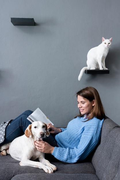 Vrouw thuis met kat en hond Gratis Foto