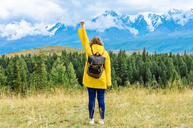 Vrouw toerist met een rugzak kijkt naar de bergen in een veroveraar pose. Premium Foto