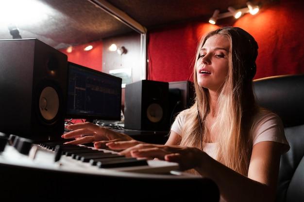 Vrouw toetsenbord bespelen en de muziek voelen Gratis Foto
