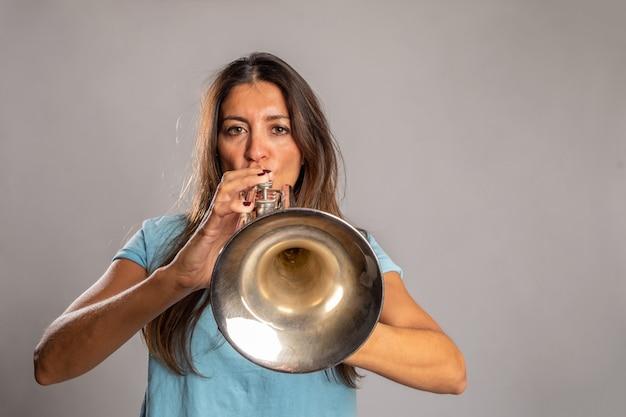 Vrouw trompet spelen op een grijze ruimte Premium Foto