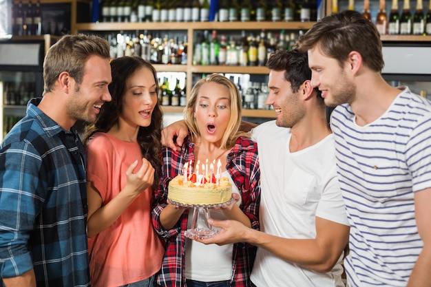 Vrouw uitblazen kaarsen terwijl vrienden kijken Premium Foto