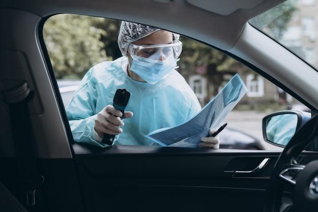 Vrouw van de arts gebruikt infrarood thermometer pistool om de lichaamstemperatuur te controleren Gratis Foto