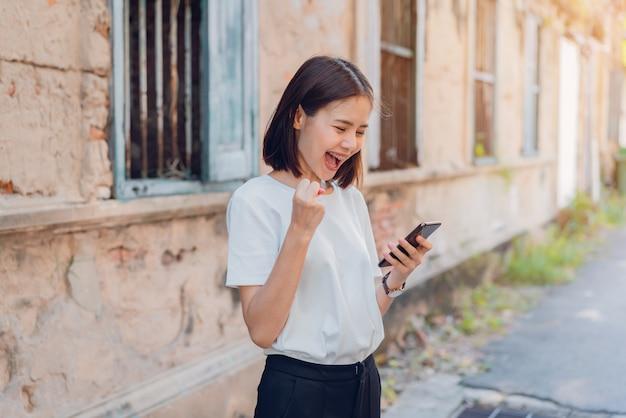 Vrouw van gelukkig glimlachend en slimme telefoon met verbaasd houden voor succes Premium Foto