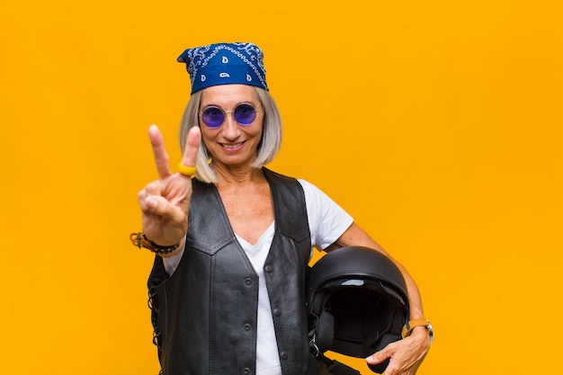 Vrouw van middelbare leeftijd die gelukkig, zorgeloos en positief glimlacht en kijkt, met één hand overwinning of vrede gebaart Premium Foto