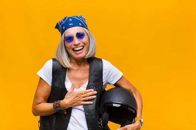 Vrouw van middelbare leeftijd die hardop lacht om een of andere hilarische grap, zich gelukkig en opgewekt voelt, plezier heeft Premium Foto