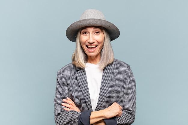 Vrouw van middelbare leeftijd met een grote, vriendelijke, zorgeloze glimlach, die er positief, ontspannen en gelukkig uitziet, huiveringwekkend Premium Foto