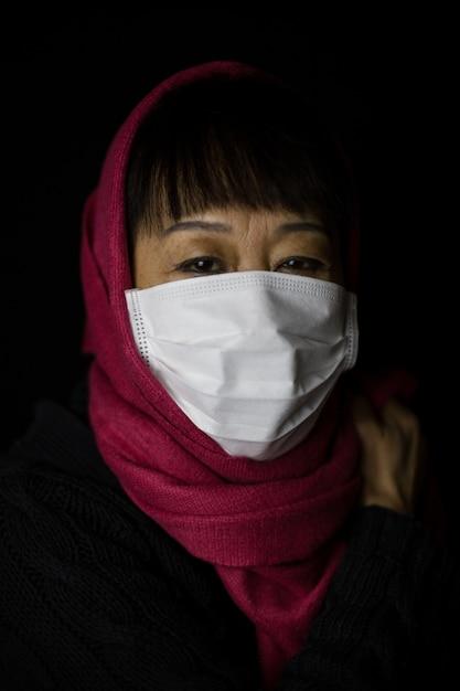 Vrouw van middelbare leeftijd met een kastanjebruine hijab die een gezichtsmasker draagt op zwarte achtergrond - coronavirus-concept Gratis Foto