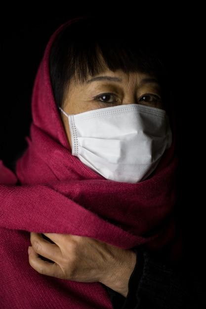 Vrouw van middelbare leeftijd met een kastanjebruine hijab die een gezichtsmasker op zwart draagt Gratis Foto