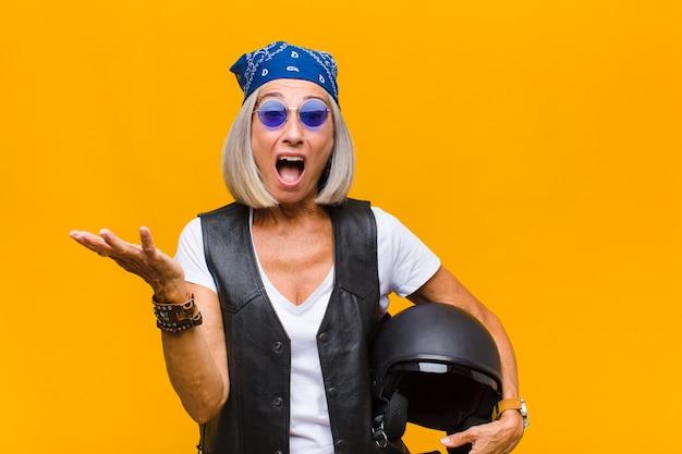 Vrouw van middelbare leeftijd met open mond en verbaasd, geschokt en verbaasd over een ongelooflijke verrassing Premium Foto