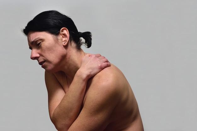 Vrouw van middelbare leeftijd met pijn in de schouder Premium Foto