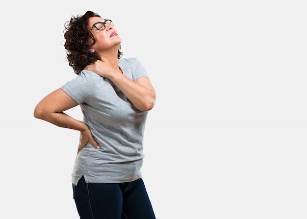 Vrouw van middelbare leeftijd met rugpijn door werkstress, moe en scherpzinnig Premium Foto