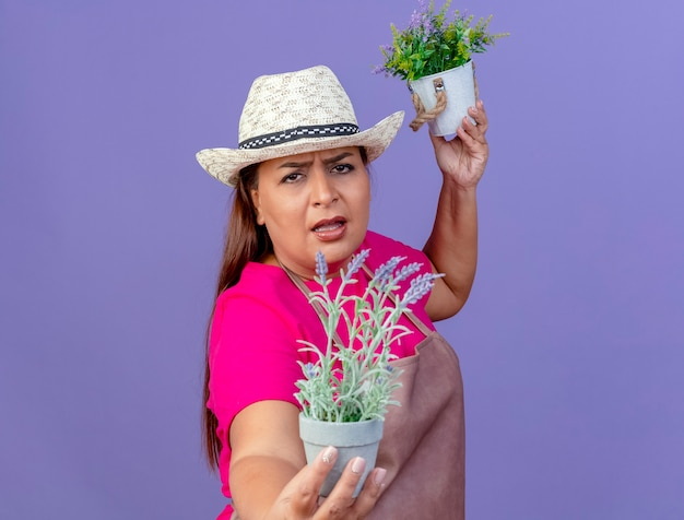 Vrouw van middelbare leeftijd tuinman in schort en hoed bedrijf potplanten camera kijken met boos gezicht staande over paarse achtergrond Gratis Foto