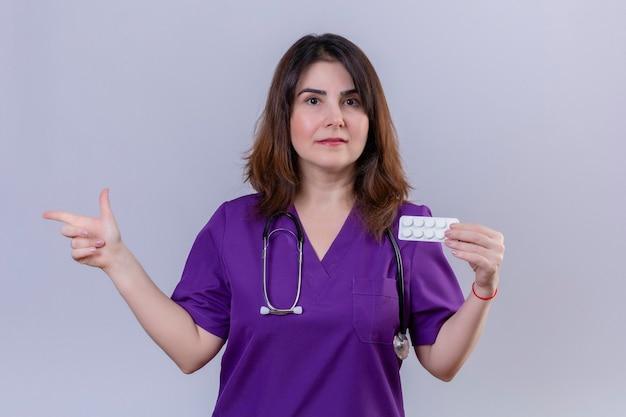 Vrouw van middelbare leeftijd verpleegster medische uniform dragen en met een stethoscoop houden blister met pillen camera kijken met ernstig gezicht wijzend met vinger naar de zijkant staande over witte chtergro Gratis Foto