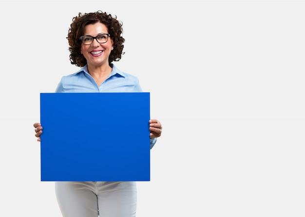 Vrouw van middelbare leeftijd, vrolijk en gemotiveerd, toont een lege poster waar je een mes kunt laten zien Premium Foto