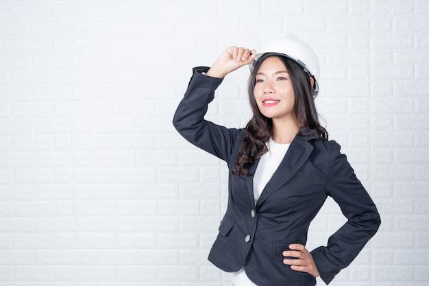Vrouw van techniek die een hoed houdt, scheid de witte bakstenen muur gemaakte gebaren met gebarentaal. Gratis Foto