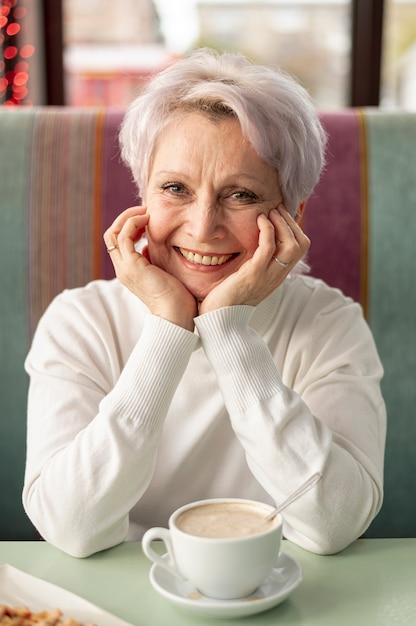 Vrouw van vooraanzicht de oudere smiley bij restaurant Gratis Foto
