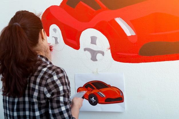 Vrouw verf kleine auto Premium Foto