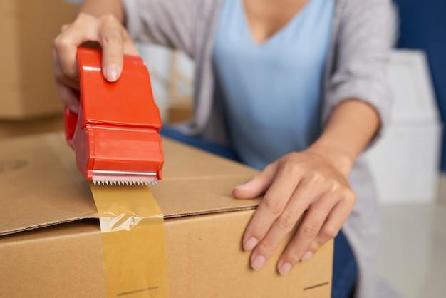 Vrouw verpakking doos met tape Gratis Foto