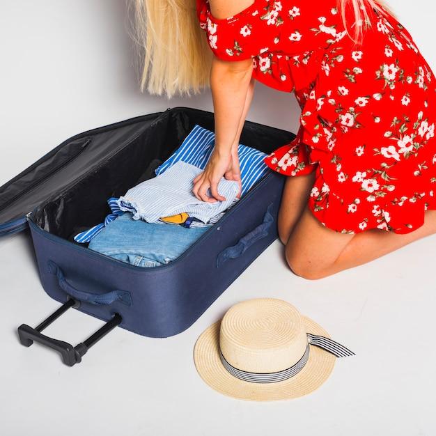 Vrouw verpakking koffer voor reis Gratis Foto
