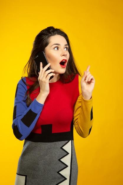 Vrouw verrast tijdens het praten via de telefoon Gratis Foto