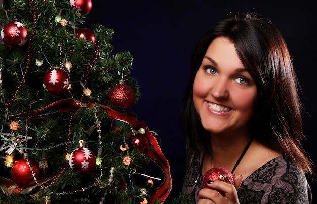 Vrouw versieren de kerstboom Gratis Foto