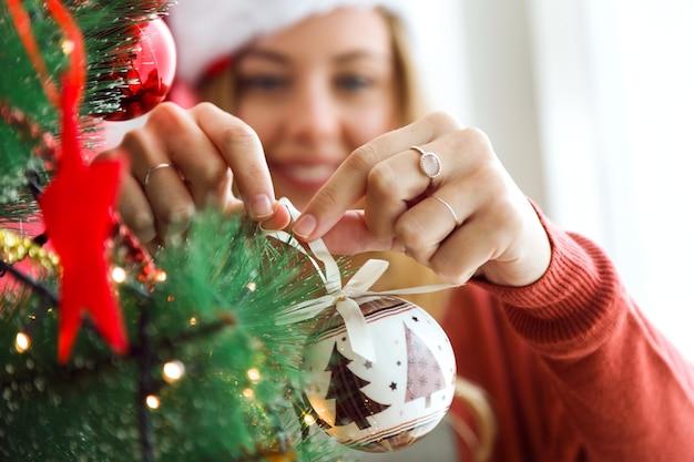 Vrouw versieren van de kerstboom met een witte bal Premium Foto