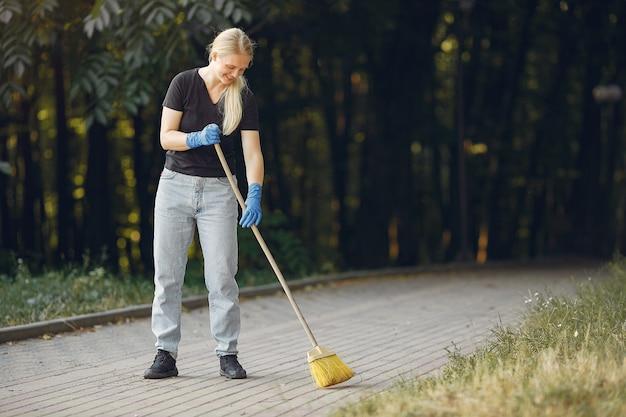 Vrouw verzamelt bladeren en maakt het park schoon Gratis Foto