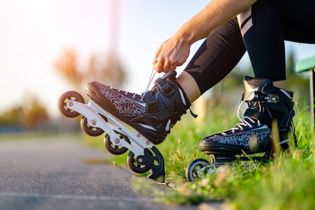 Vrouw veters rolschaatsen voor inline skaten. tiener skaten buitenshuis. Premium Foto