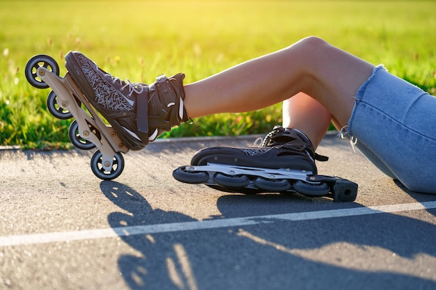 Vrouw viel op asfalt tijdens skaten. inline skaten zonder bescherming Premium Foto