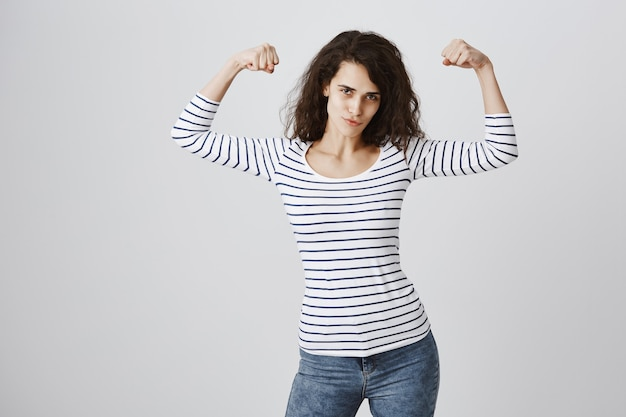 Vrouw voelt zich bevoegd buigen biceps na training Gratis Foto