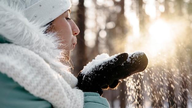 Vrouw waait sneeuw buiten in de winter Premium Foto