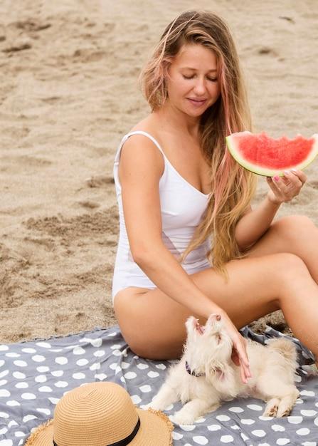 Vrouw watermeloen eten op het strand met hond Premium Foto
